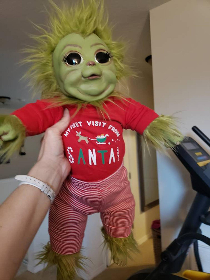 hand carrying a baby grinch doll