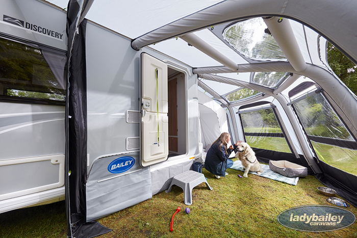 lady and a dog under an rv inflatable awning