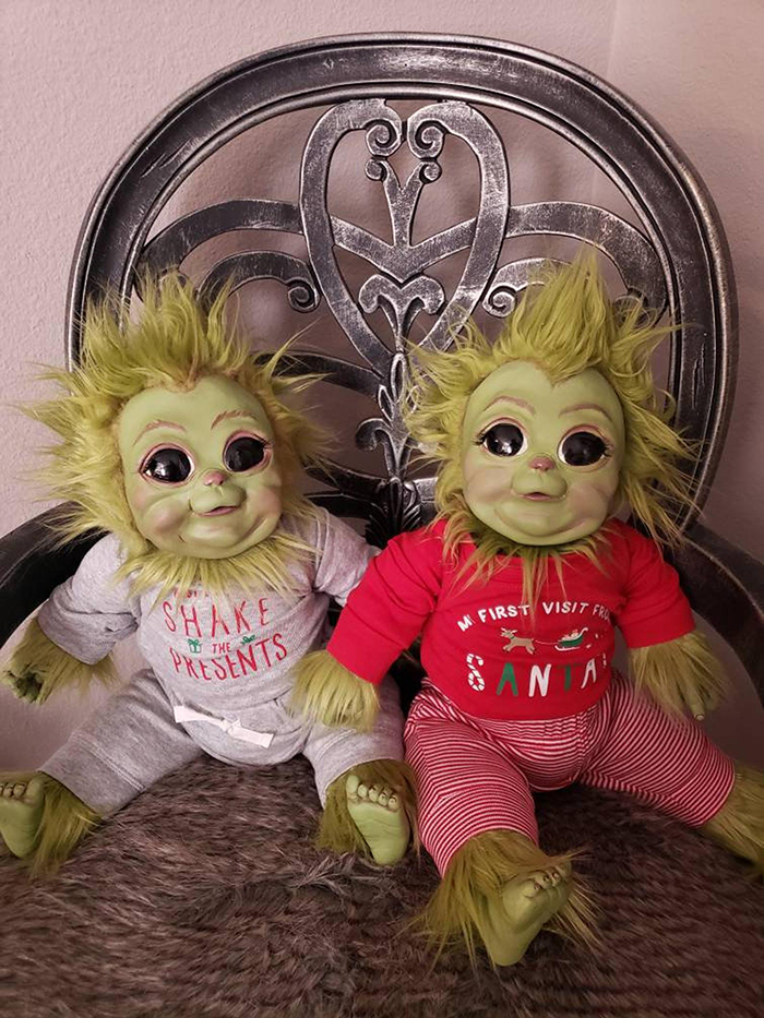 two baby grinch dolls sitting on couch