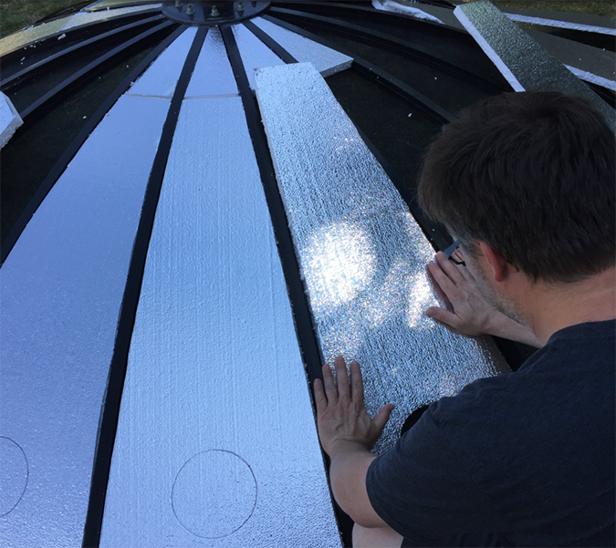 Brett installs Styrofoam insulation over the satellite dish and draws circular outlines for the windows