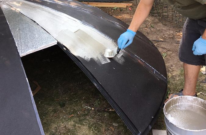 Brett paints aluminum paint over the roof felt