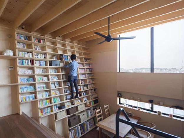 Shin Yoshida stands on his earthquake-proof bookshelf