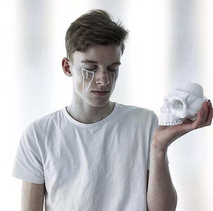 man holding a cranium-inspired candle holder