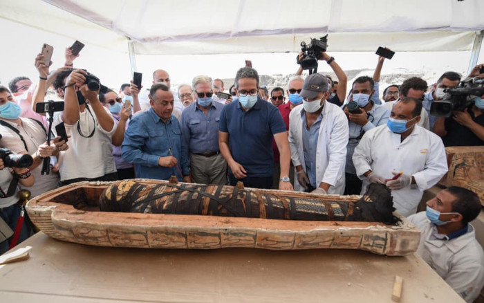 members of the ministry of tourism and antiquities media and dignitaries crowd around the opened Egyptian coffin