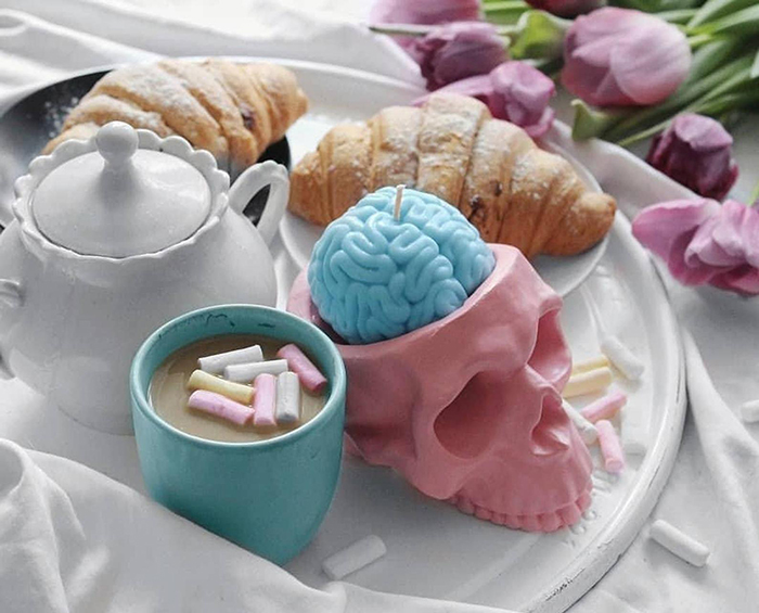 pastel blue human brain candle in pink skull holder