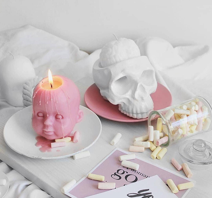 pink baby head candle and cranium-inspired candle holder