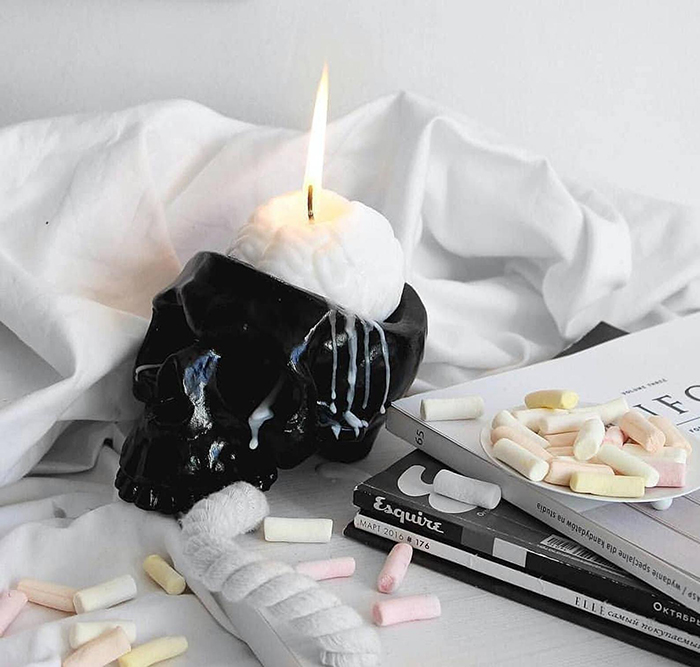 white human brain candle in black skull holder