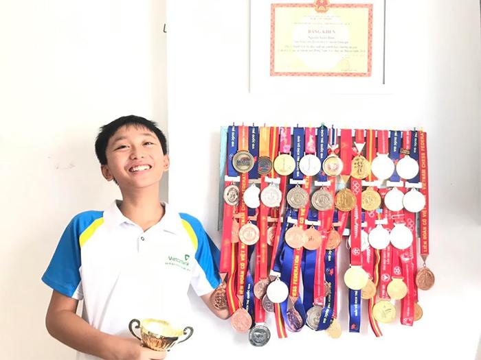 kid flexes chess medals