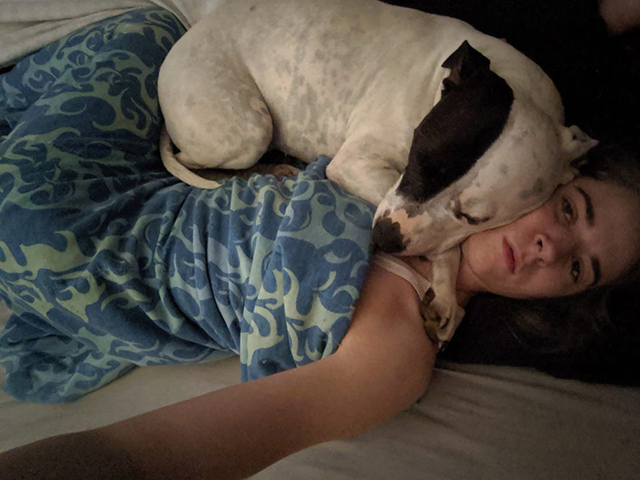 adopted dog cuddling new owner while sleeping