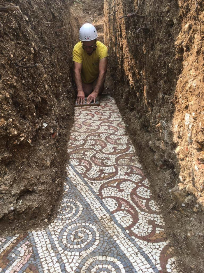 an archaeologist carefully removes the soil from the ancient roman mosaic floor