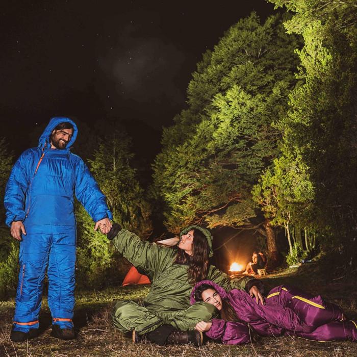 campers in blue green and purple sleeping bag onesie suits