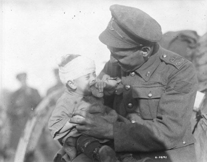 canadian soldier comforts a crying belgian baby