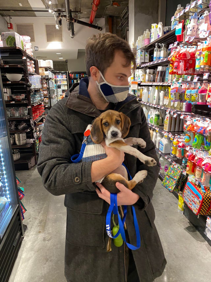 man carrying adopted puppy while shopping