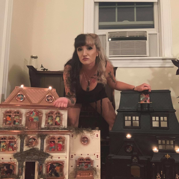Samantha Browning poses with her the dollhouses