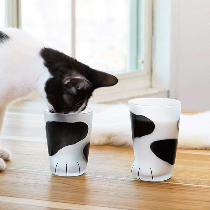feline drinking from feline claw glass