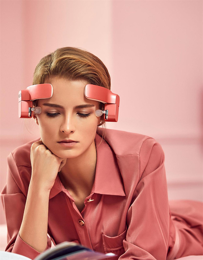 lady wearing head-mounted massage robot while reading book