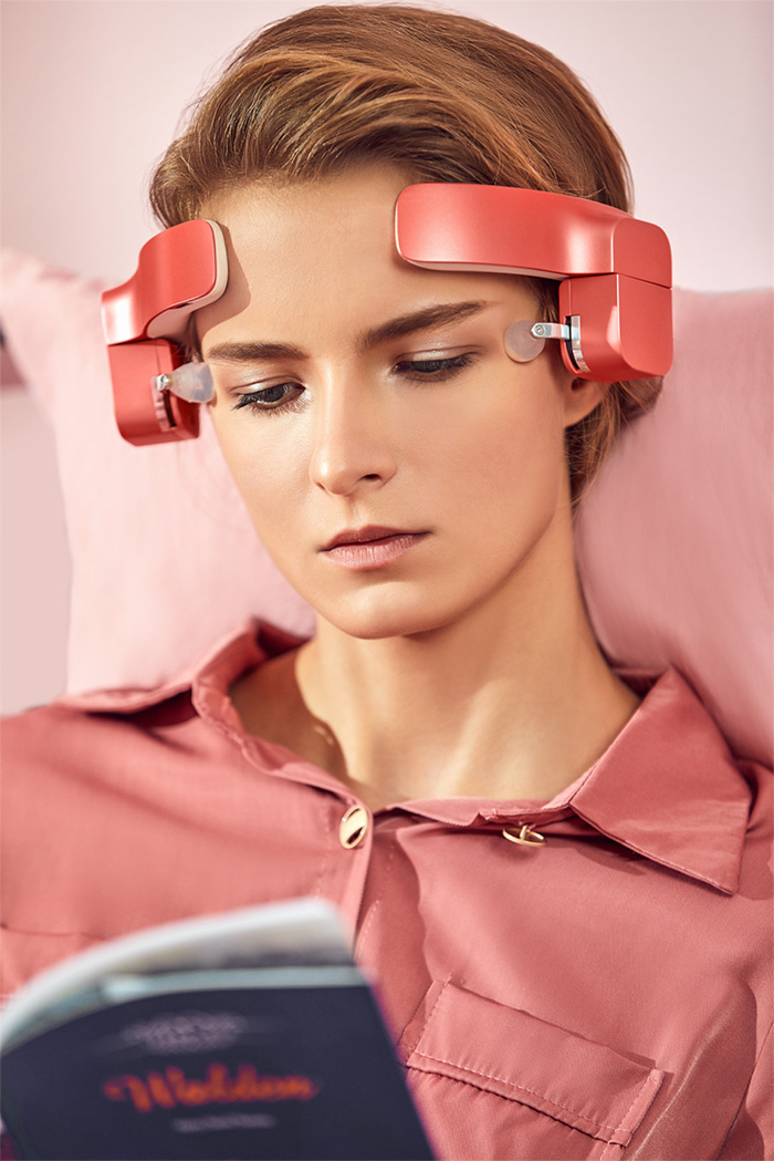 lady wearing head-mounted massage robot while reading