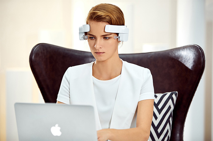 lady wearing head-mounted massage robot while working