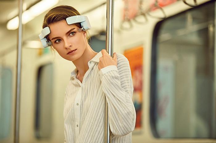 lady wearing lerou head massenger while on train