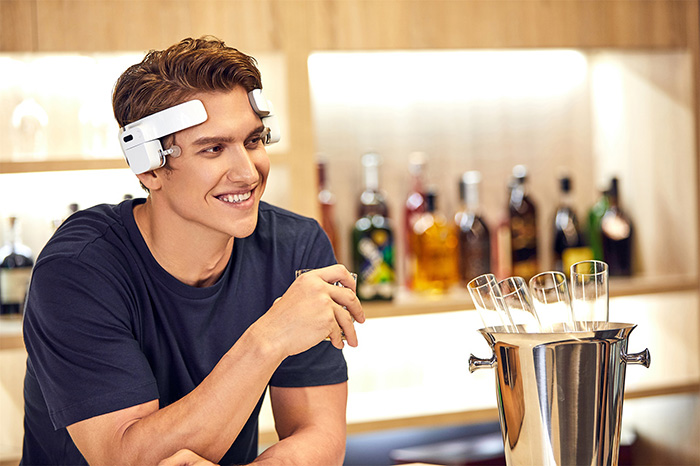 man wearing head massager while drinking alcohol