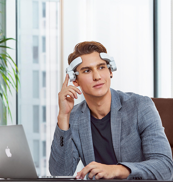 man wearing head-mounted massage robot in the office