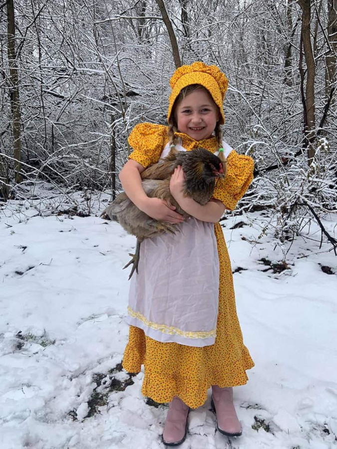 Melissa Tomas' daughter dons a yellow prairie dress and cuddlse a fluffy hen in the snow
