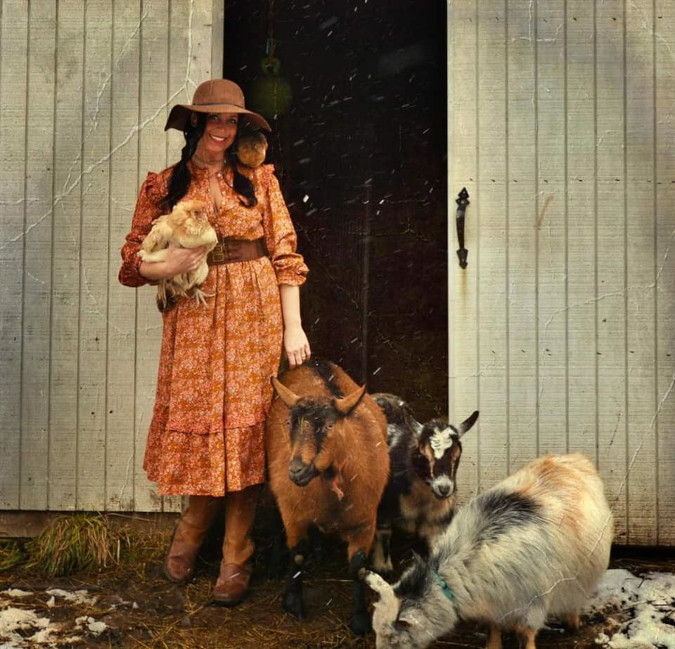 a woman grins as she poses alongside farm animals in her roasting entry