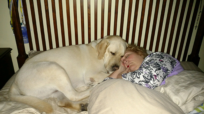 dog sleeping on bed beside owner's wife