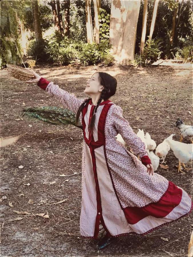 little girl gracefully poses in red prairie dress