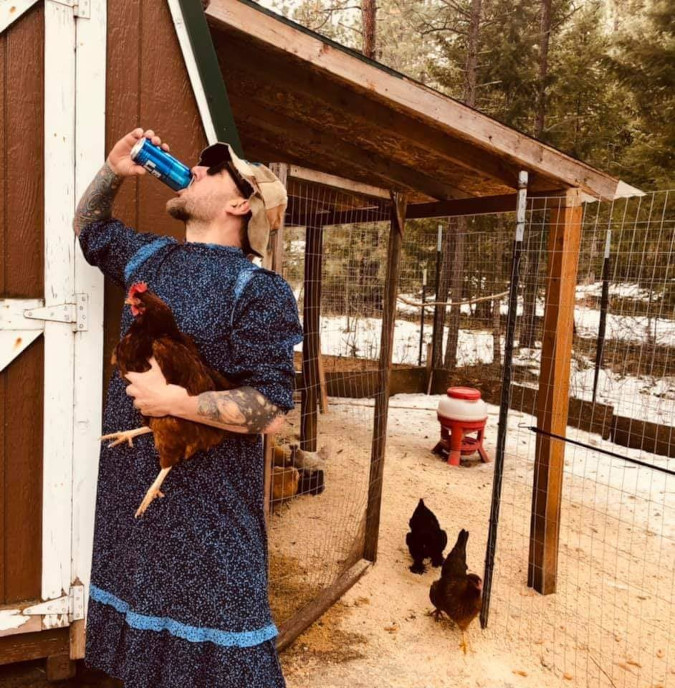 man chugs a drink and holds a fat hen while roasting target