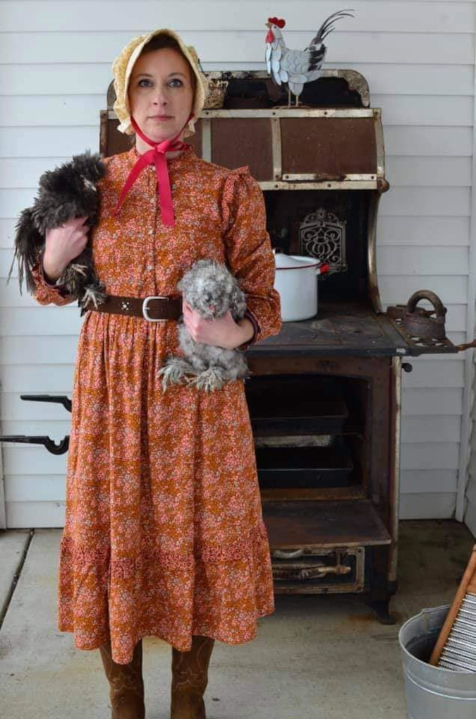 woman wins the target dress roasting event by posing with chickens and an ancient stove