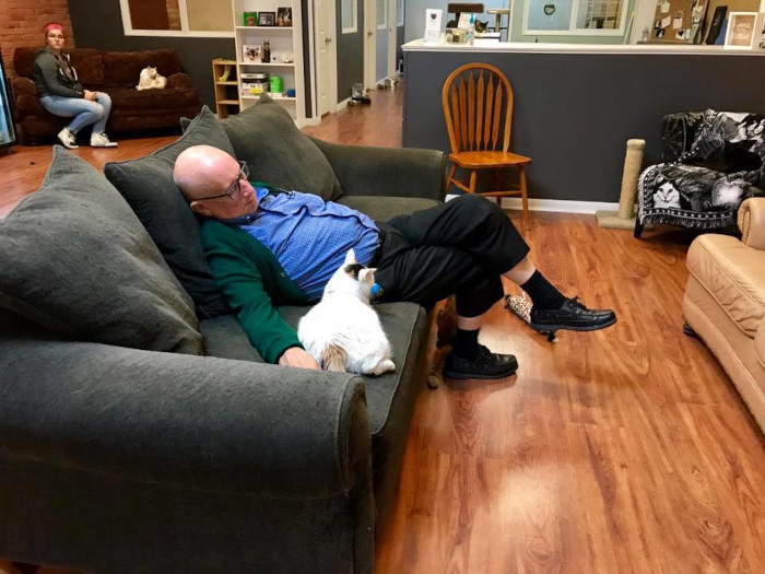 Safe Haven Pet Sanctuary volunteer Terry naps with one of the shelter cats