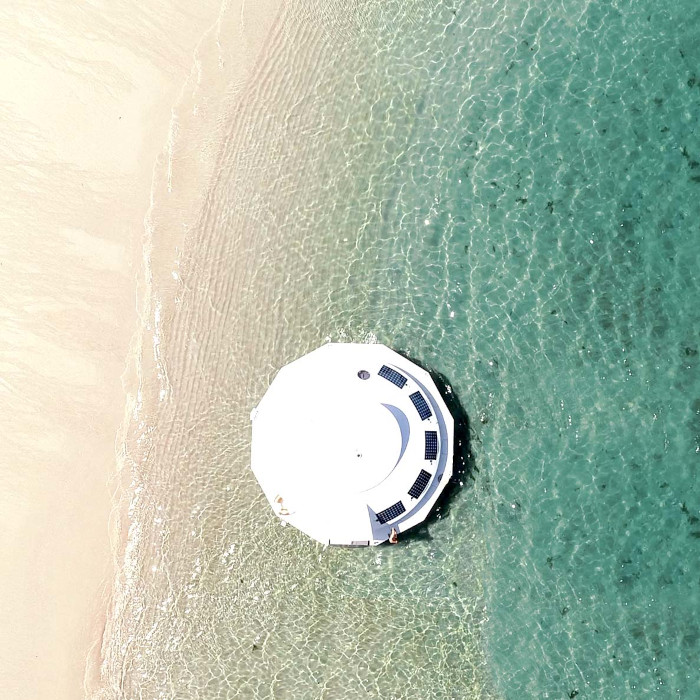 aerial shot of the Anthenea by the sea shore