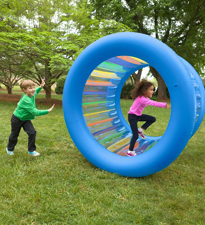 kids playing outdoors with blow up running wheel