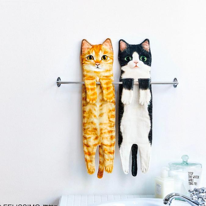 orange tabby and british shorthair cat shaped towels dangling on towel rack