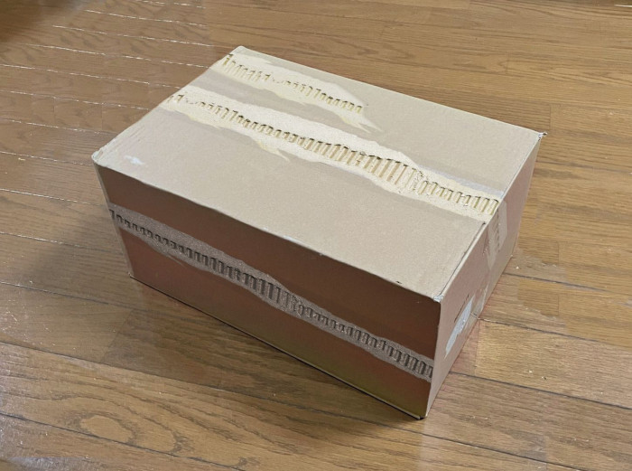 ripped packing tape used on a plain cardboard box
