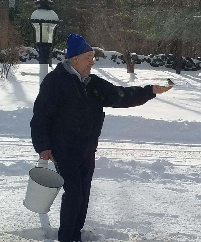 old people being wholesome man feeding bird in snow
