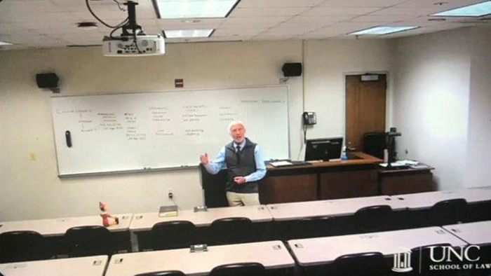 old people being wholesome professor conducting online class with pinocchio doll