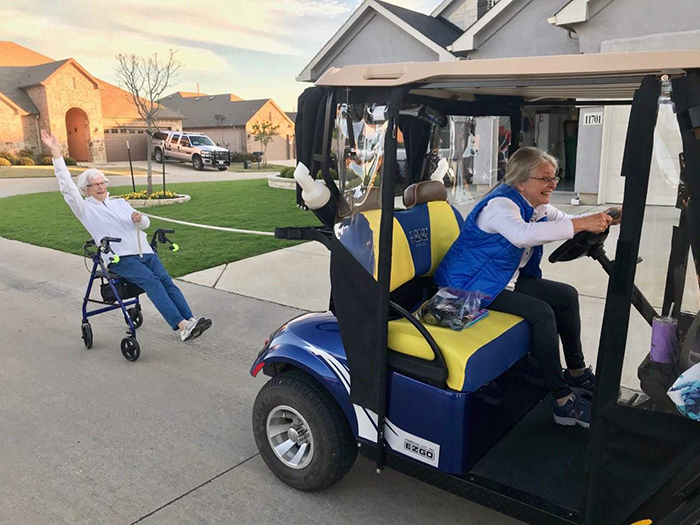 old people being wholesome women in retirement community driving golf cart