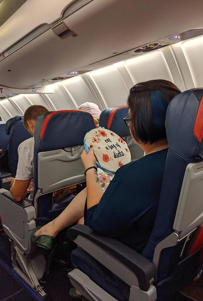 woman cross-stitching on plane